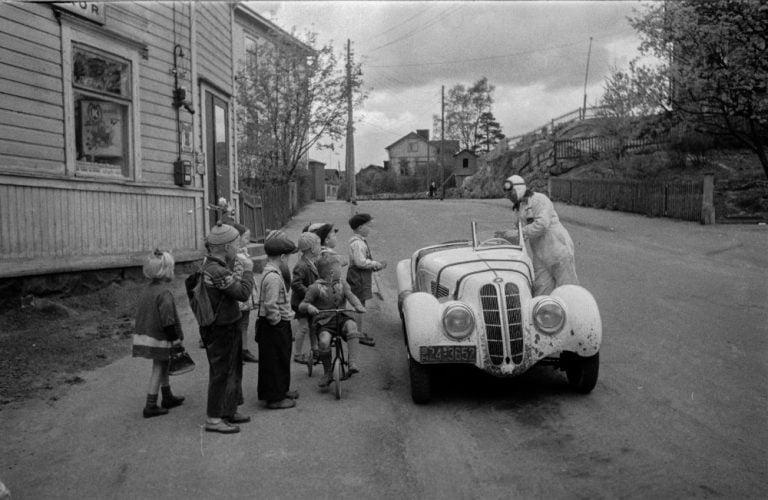 Päivän autourheilukuva: Lapsia ihmettelemässä Leo I. Mattilan BMW-autoa kaupan edessä Helsingin Pasilassa